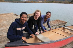 students with boat at the lake