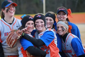 female softball teammates smiling after a win