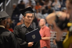 graduate with diploma at graduation ceremony