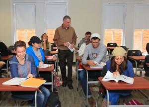 teacher walking through rows of students at desks