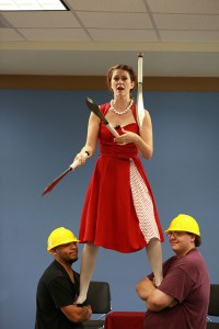 woman juggling while being held up by two men