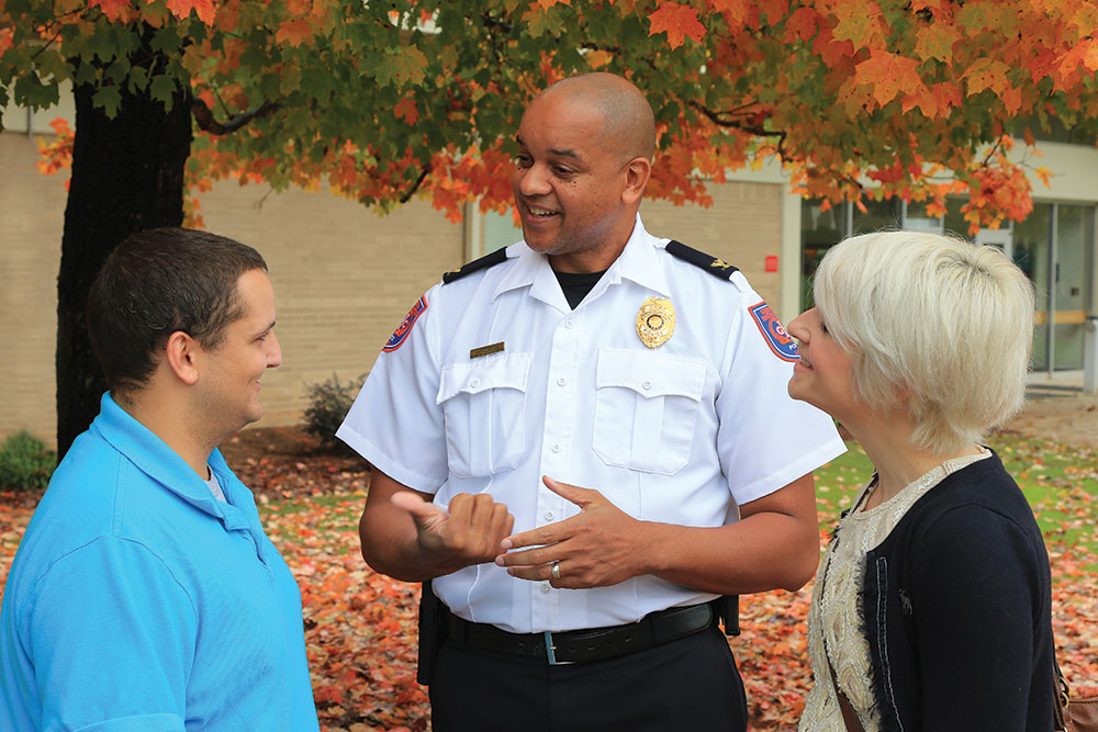 Campus Safety officer talking with two students