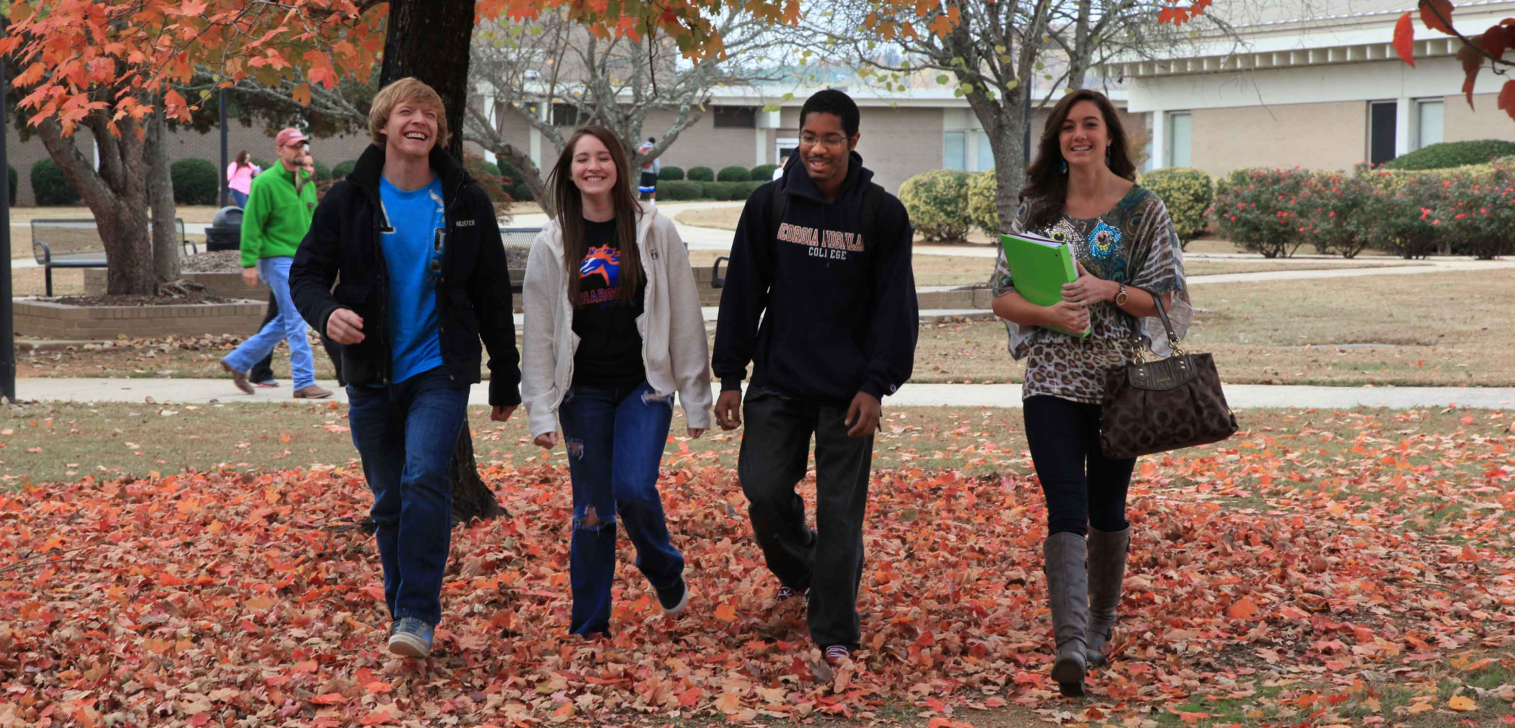 four students walking in the leaves