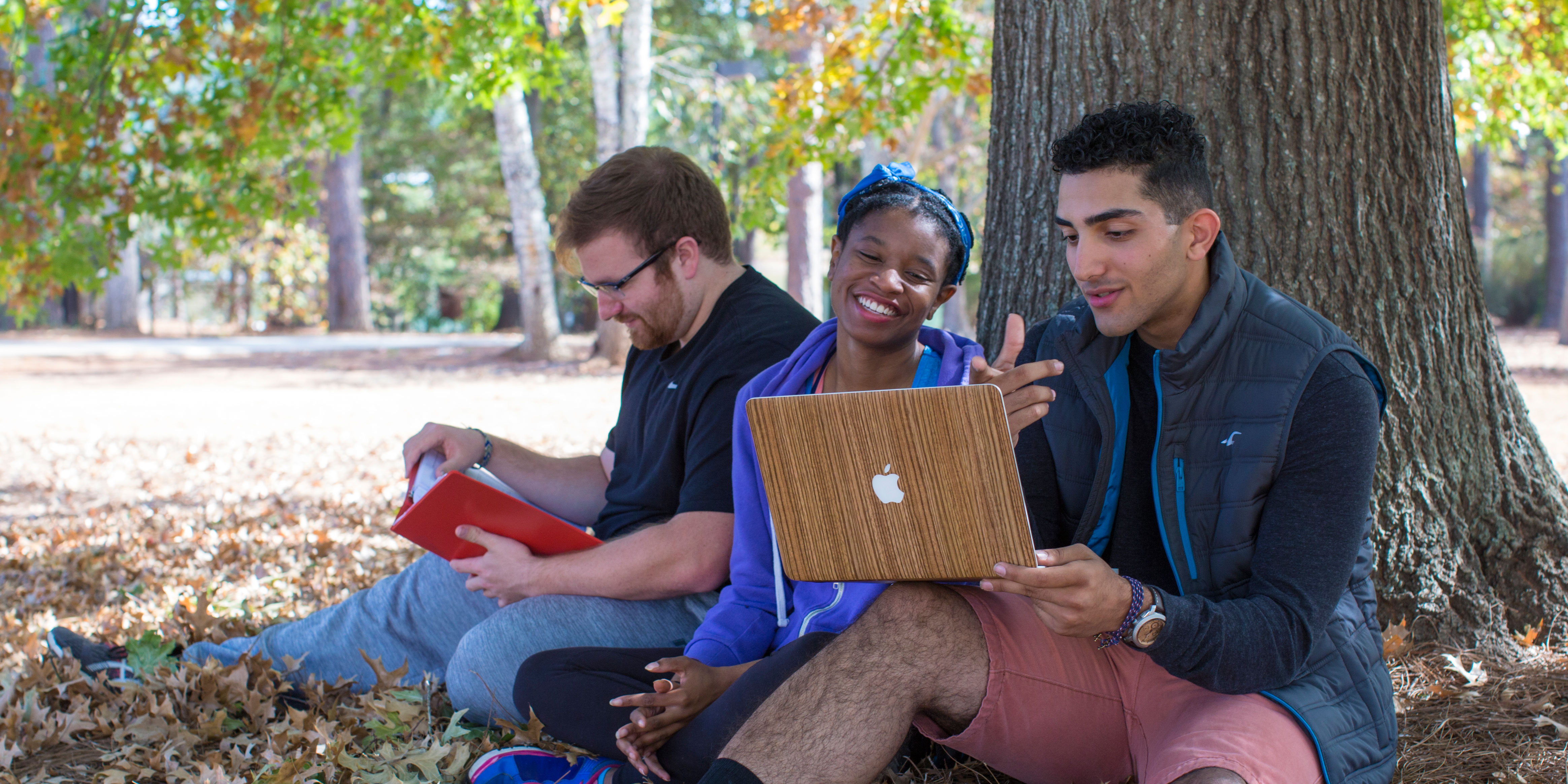GHC students sitting around laptop under tree