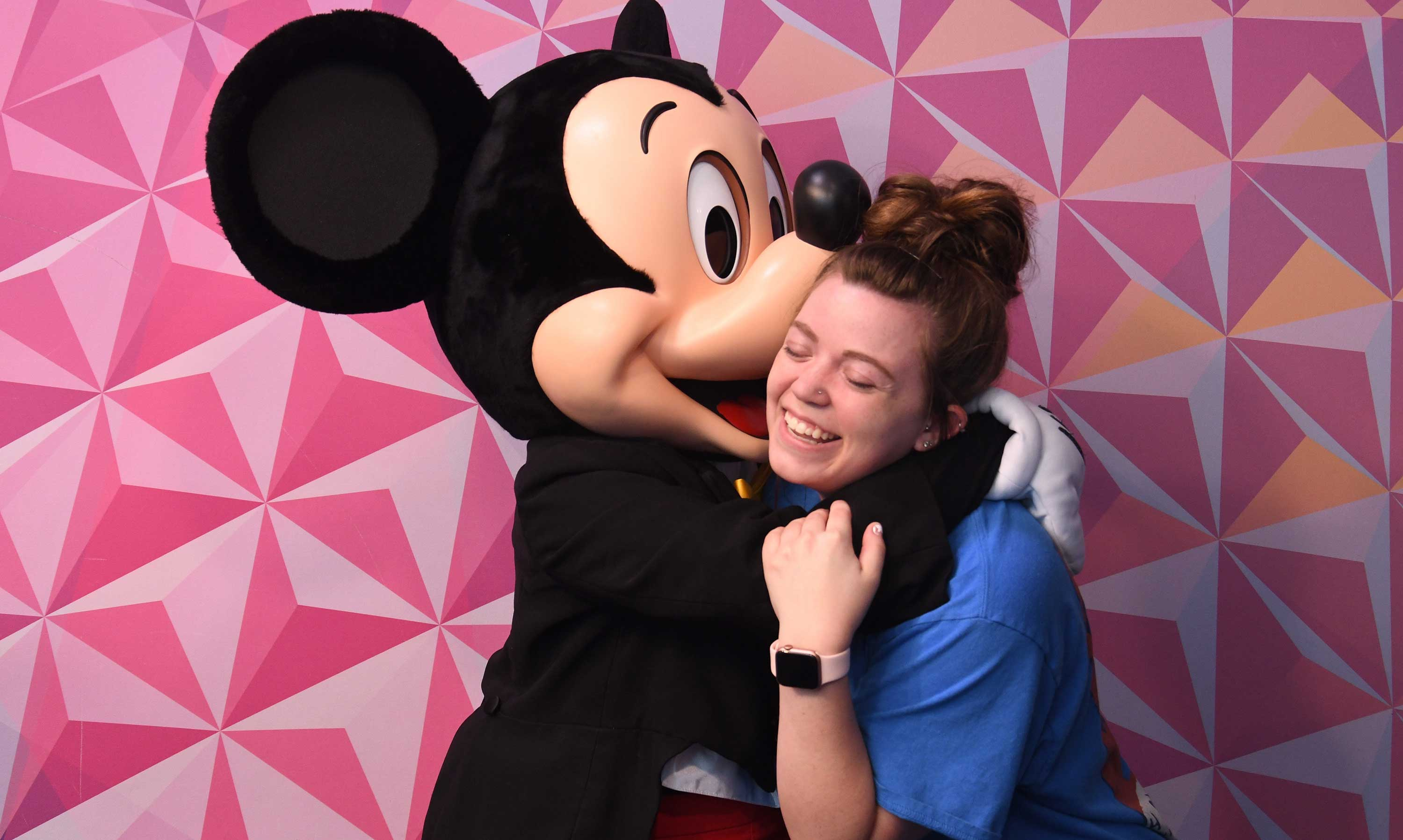 Mickey Mouse hugging student.